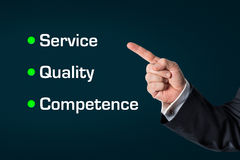 Business man pointing at the words -Service, Quality, Competence. Business man pointing at the words,Service-Quality-Competence ,with an dark blue background royalty free stock image