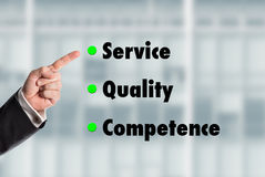 Business man pointing at the words, Service-Quality-Competence. With an office facade in the background stock image