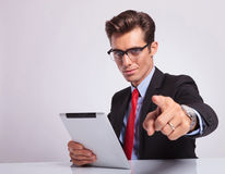 Business man pointing. Young business man sitting at the desk and pointing at the camera while holding a tablet in his other hand and looking at the camera Stock Photos