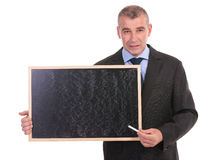 Business man points with chalk on blackboard Stock Image