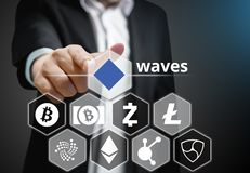 Business man points his finger at Waves coin icon. Among others Cryptocurrency on Virtual Touch Screen , Conceptual royalty free stock photo