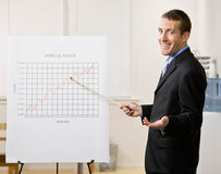 Business man points to sales graph stock photo