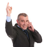 Business man points up while on phone Stock Images