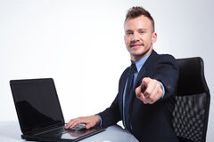 Business man points at you from his desk Stock Photos