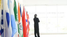 Business man or politician walk from right corner and stand in front of International flags stock video
