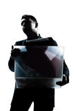 Business man portrait carrying heavy box. One caucasian business man portrait silhouette carrying heavy box in studio isolated white background Stock Image