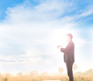 Business man pray. Business man that face covey by strong sun light, standing and pray under blue sky white cloud Stock Photo