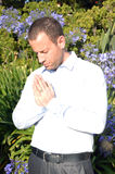 Business man praying outside by purple flowers. Stock Images