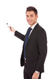 Business man presenting with marker. Handsome young business man in a suit pointing with a pen on white background stock image