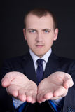 Business man presenting something on his hand over grey Stock Photography