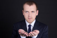 Business man presenting something on his hand. Young business man presenting something on his hand Royalty Free Stock Photos