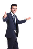 Business man presenting something and showing thumbs up Stock Photography