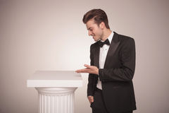 Business man presenting something on a white column. Royalty Free Stock Image
