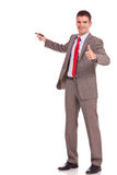 Business man presenting and thumbs up. Smiling young business man presenting something with marker pen and giving the thumbs up stock image