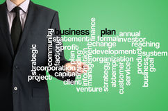 Business man presenting wordcloud related to business plan on vi. Business man presenting wordcloud related black text by his hand royalty free stock photos