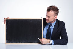Business man presents on chalkboard Royalty Free Stock Images