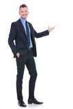 Business man presents with hand in pocket Stock Image