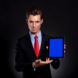 Business man presents tablet. Portrait of a young business man standing against a black background presenting a tablet with a faint smile on his face Stock Photo