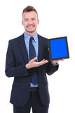 Business man presents a tablet with a smile Stock Photo