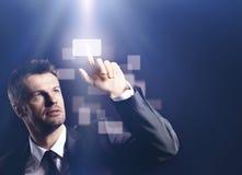 Business man pressing virtual button on black background Stock Photos