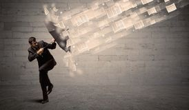 Business man protecting with umbrella against wind of papers. Concept Royalty Free Stock Photos