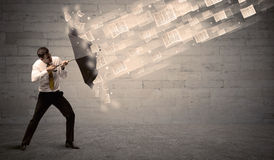 Business man protecting with umbrella against wind of papers Stock Images