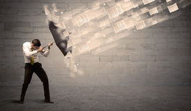Business man protecting with umbrella against wind of papers Royalty Free Stock Photography