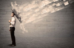 Business man protecting with umbrella against wind of papers Stock Photography