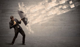 Business man protecting with umbrella against wind of papers Royalty Free Stock Photos