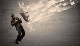 Business man protecting with umbrella against wind of papers Stock Photos