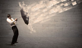 Business man protecting with umbrella against wind of papers Royalty Free Stock Image