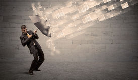 Business man protecting with umbrella against wind of papers Royalty Free Stock Photo