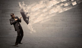 Business man protecting with umbrella against wind of papers Stock Image