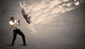 Business man protecting with umbrella against wind of papers Stock Photo