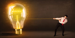 Business man pulling a big bright glowing light bulb Royalty Free Stock Image