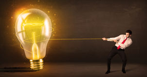 Business man pulling a big bright glowing light bulb Royalty Free Stock Photos