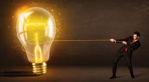 Business man pulling a big bright glowing light bulb Stock Image