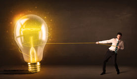 Business man pulling a big bright glowing light bulb Royalty Free Stock Photography