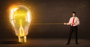 Business man pulling a big bright glowing light bulb Royalty Free Stock Images