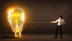 Business man pulling a big bright glowing light bulb. Concept on background Stock Images