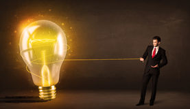 Business man pulling a big bright glowing light bulb Stock Photo
