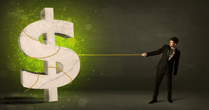 Business man pulling a big green dollar sign Stock Image