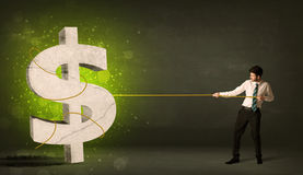 Business man pulling a big green dollar sign Royalty Free Stock Image