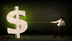 Business man pulling a big green dollar sign Stock Photography