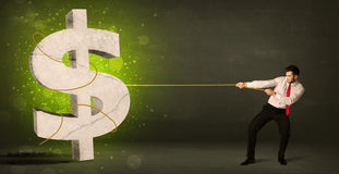 Business man pulling a big green dollar sign. Concept on background Royalty Free Stock Image