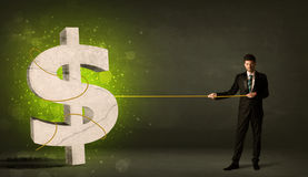 Business man pulling a big green dollar sign Royalty Free Stock Images