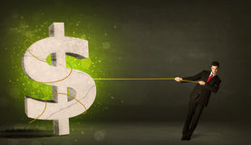 Business man pulling a big green dollar sign. Concept on background stock image