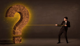 Business man pulling a big solid question mark stone Royalty Free Stock Photography
