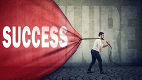 Business man pulling a red banner with success word overcoming a failure royalty free stock photos