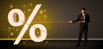 Business man pulling rope with big procent symbol sign Royalty Free Stock Photos